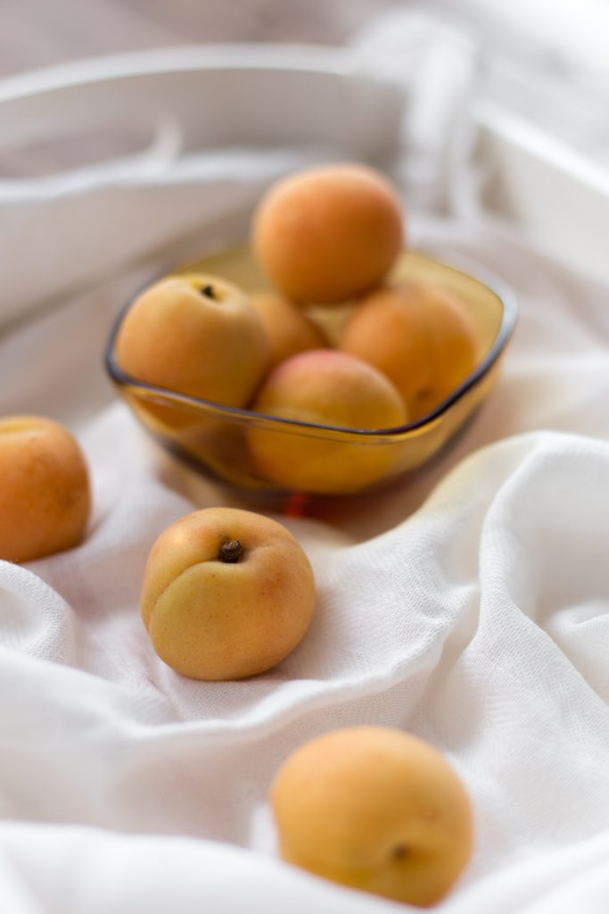 picture of peaches, bowl of peaches on white cloth